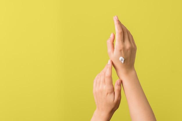 Крупный план нежных рук молодой женщины с увлажнителем дальше против желтой предпосылки. защита кожи весной