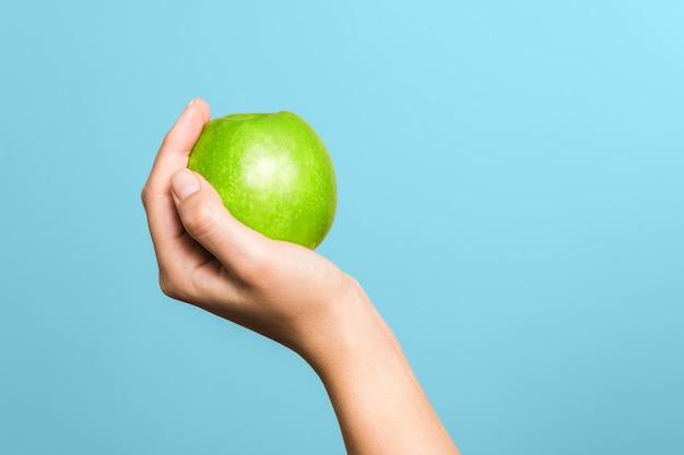 Закройте вверх по руке женщины держа зеленое яблоко против голубой предпосылки. выбирая здоровый образ жизни