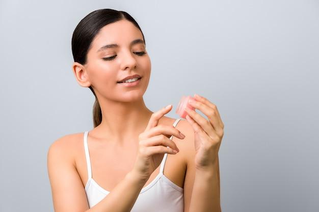 季節の皮膚保護。灰色の壁に対してリッププロテクションバームを適用する女性を笑顔します。
