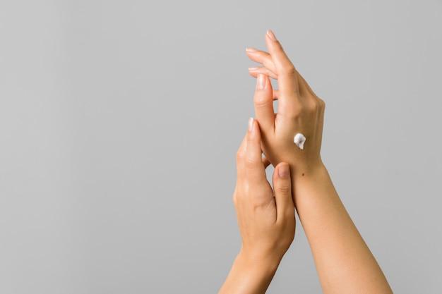 Здоровые руки молодой женщины, применяющей солнцезащитный крем