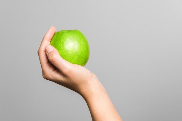 Женская рука держит зеленое яблоко на серой стене