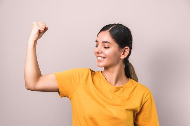 Привлекательная улыбающаяся брюнетка в желтой футболке показывает бицепс на розовой стене