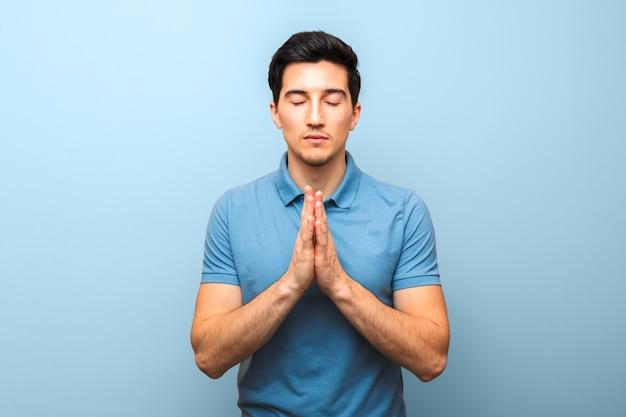 Мужчина в синей рубашке молится против синей стены