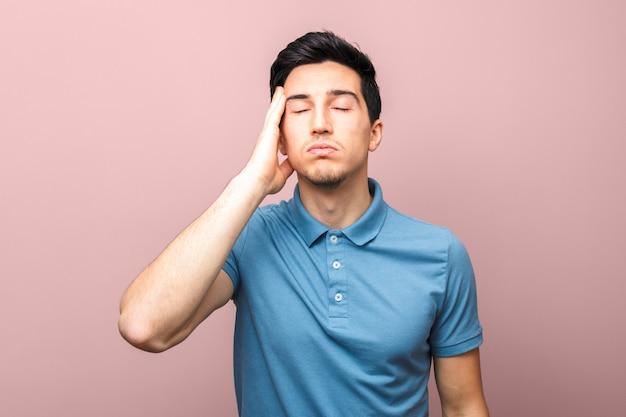 Взрослый человек в синей рубашке с головной болью, держа руку на висок, стоя у розовой стены