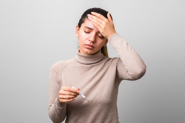 Расстроен молодая женщина со стеклянным термометром в руках с высокой температурой