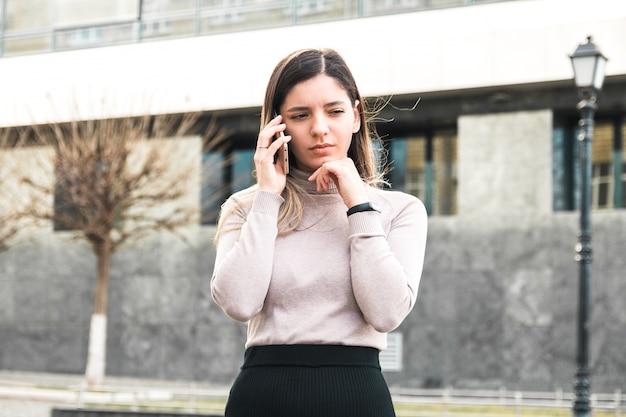 Молодая деловая женщина получает плохие новости по телефону из-за мирового кризиса, выглядит задумчивым и разочарованным