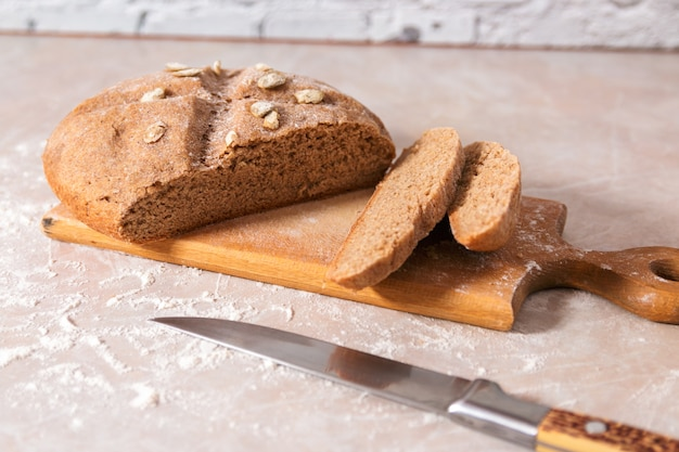 Свежий здоровый домашний хлеб с тыквенными семечками нарезанный на деревянной доске