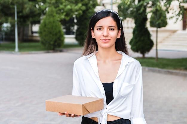 Привлекательная женщина кавказской в белой рубашке и с головкой, держа картонную коробку в ладони, открытый в городском парке. еда на вынос или концепция доставки