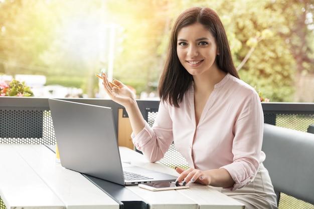 電話で見ていると、コンピューターで作業しながら笑顔の若いビジネス女性。