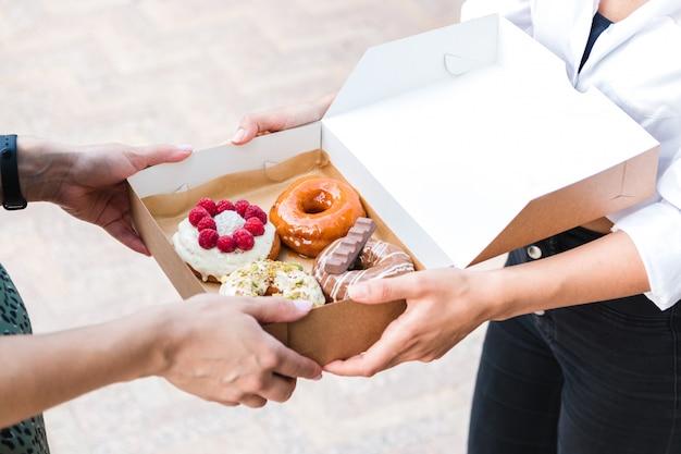 Закройте руки, держащие четыре кусочка совершенно разных красочных и вкусных пончиков в экологически чистой картонной коробке