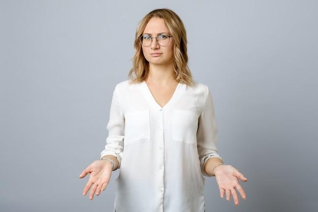 Разочарованный молодая женщина пожимает плечами с ее руки, изолированные