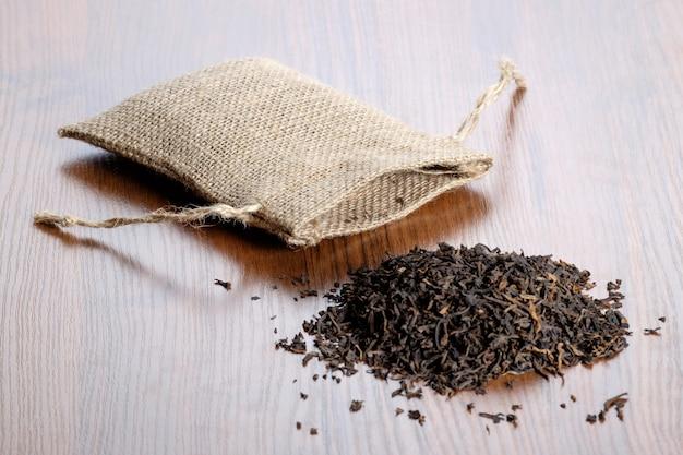 木製のテーブルにお茶とビンテージの黄麻布