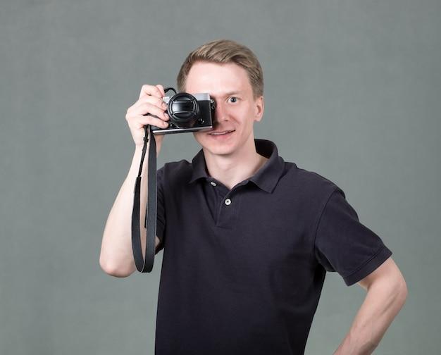 灰色の壁にカメラを持つ男