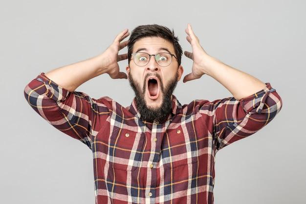 灰色で分離されたメガネで興奮して興奮した男