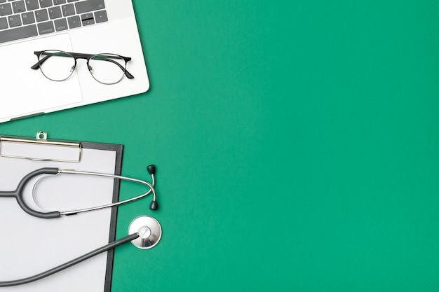 ノートパソコンと医師の机の上から見る