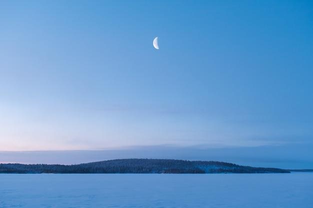 ロシアの冬の風景。森の上に昇る新月