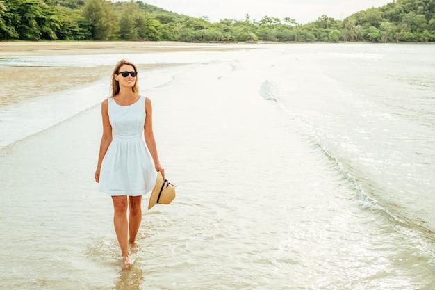 Счастливая молодая женщина в красивом белом платье гуляя на пляж