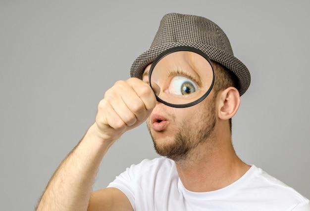 虫眼鏡を通して見るびっくりした男