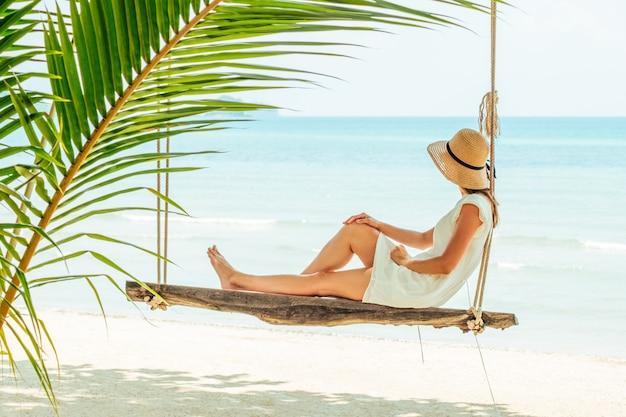 ビーチでブランコに座っている魅力的な旅行者女性