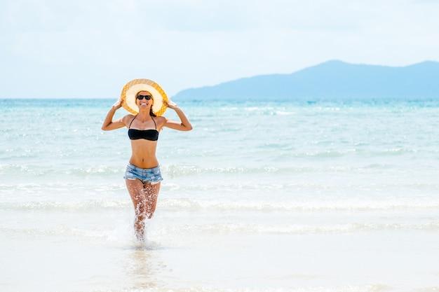 夏休みに楽しんでビキニを着て幸せな屈託のない女性