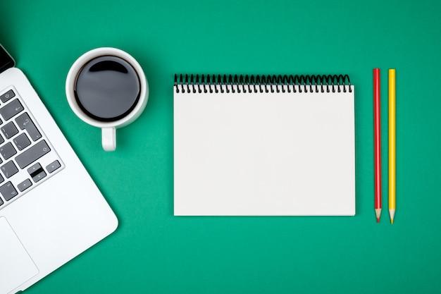 ノートパソコンと空白のノートブックページと近代的なオフィスデスクテーブル