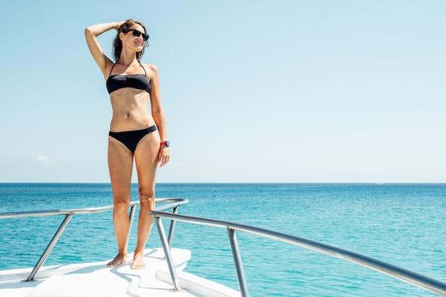 セーリングボートの船首に立っている幸せな女の子が島を発見する楽しみを持っています。