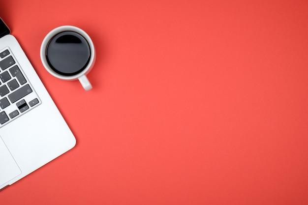 ノートパソコン、一杯のコーヒー、コピースペースとワークスペースのトップビュー