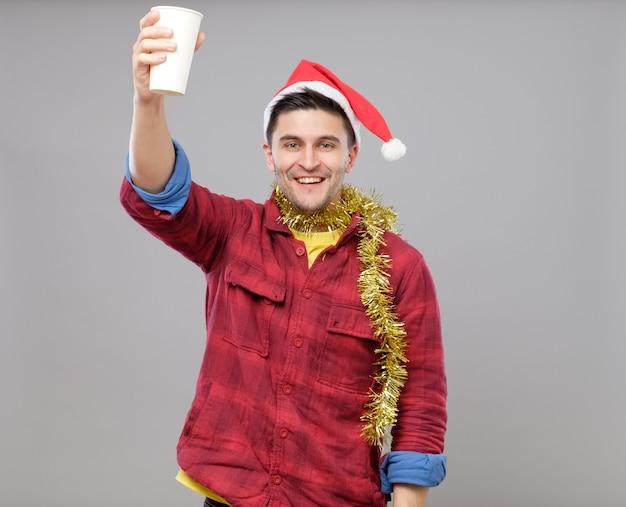 Смешной молодой пьяный мужчина в шляпе санта держит бумажный стаканчик