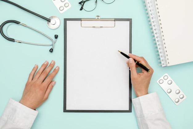 Доктор сидит на синем офисном столе и работает