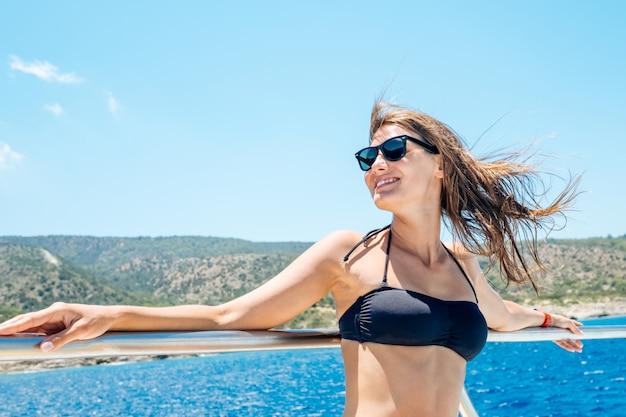 ヨット上で楽しんで幸せな女性観光客