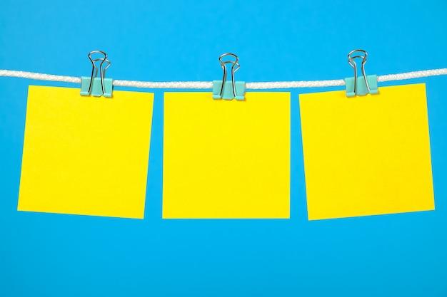 Пустые желтые бумажные заметки на веревках