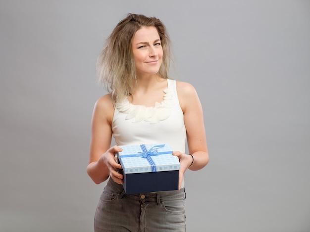 Грустная женщина, держащая подарочную коробку