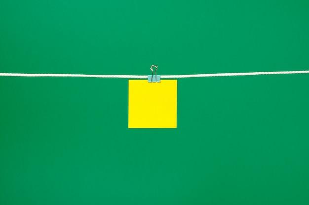 Чистый желтый лист бумаги на веревочке