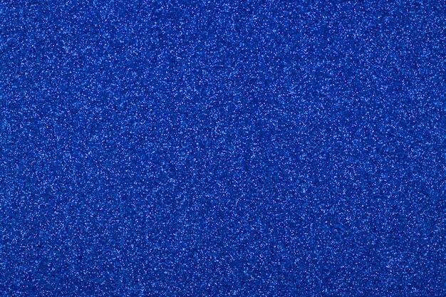青い抽象的なキラキラ背景に焦点を当てた
