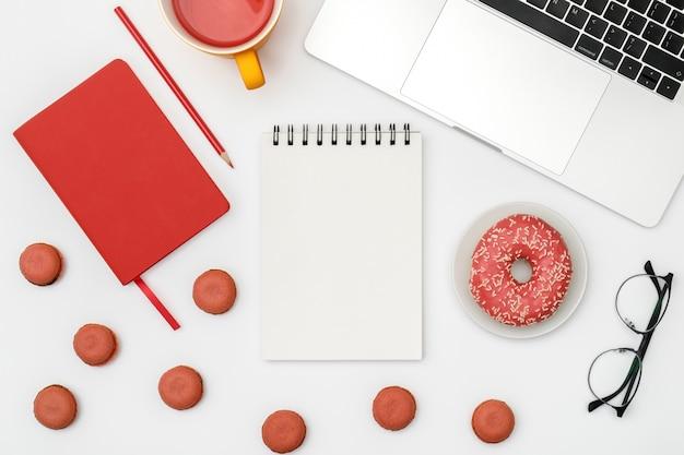 空白のノートブックページを持つ白いデザイナーオフィスデスクテーブル