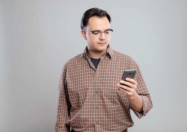 Молодой взрослый человек, с помощью мобильного телефона