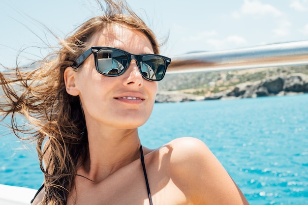 ヨットにサングラスで幸せな笑顔の美しい若い女性の肖像画