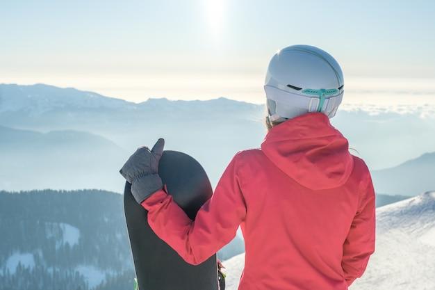 スノーボードに立って、山の風景を楽しんでいる女性のスノーボーダーの背面図
