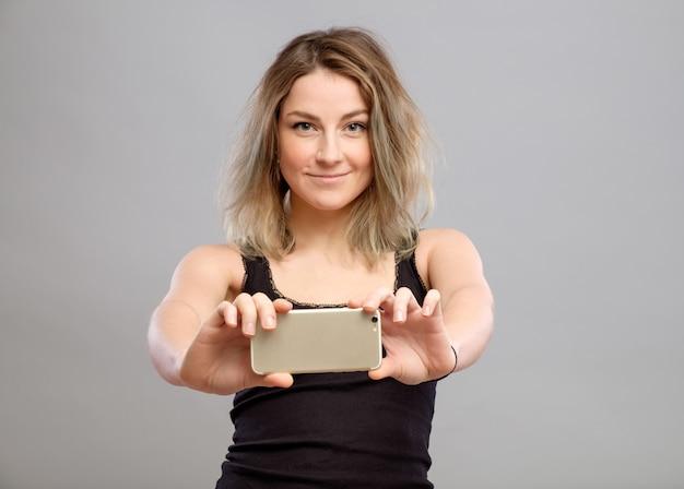 若い女性が彼女の電話で写真を撮る