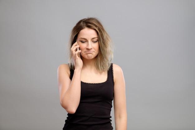Расстроенная женщина разговаривает по телефону