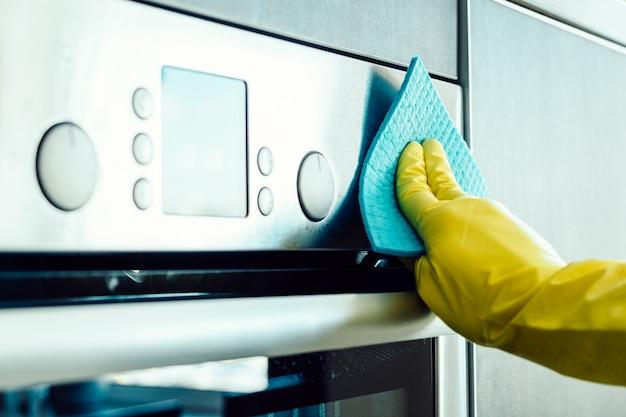 Мужская рука чистит кухонную плиту