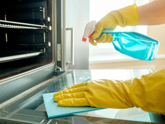 Мужская рука в перчатке с тряпкой для чистки духовки