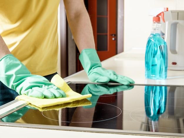 Мужчина чистит плиту на кухне