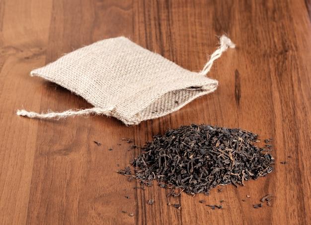 木製の背景にお茶とヴィンテージの黄麻布