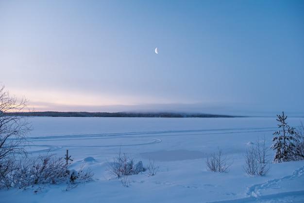 ロシアの冬の風景。森に昇る新月