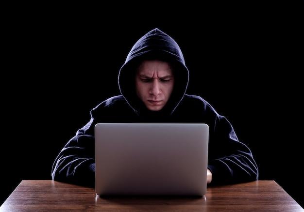 フード付きのコンピューターハッカーが情報を盗む