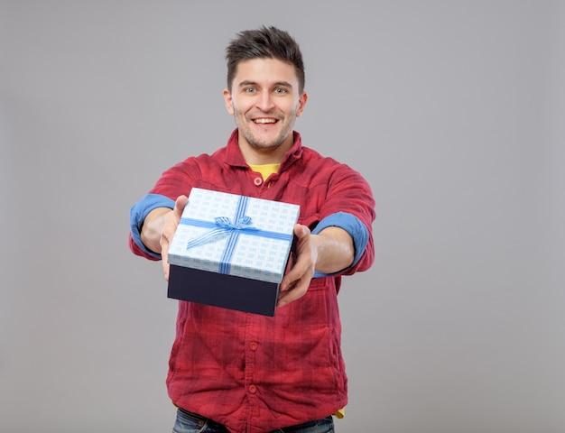 贈り物を提示する幸せな若い男の笑顔