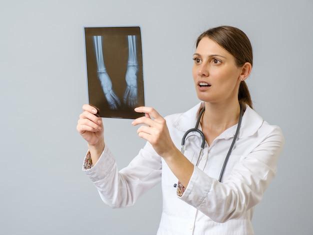 Женщина-врач изучения рентгеновского изображения ног новорожденного