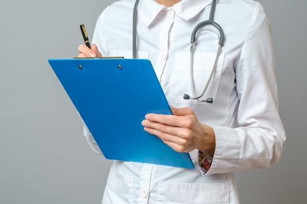 Молодая женщина врач со стетоскопом, предписывающих лечение пациенту. женский доктор с рецептом сочинительства ручки в доске сзажимом для бумаги. изолированные на серый