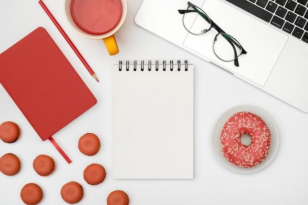 空白のノートブックページの白いデザイナーオフィスデスクテーブル